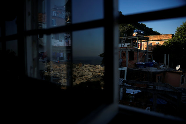 Houses (R) are seen through a window as Copacabana beach is reflected on a glass at Tiki hostel in Cantagalo favela, in Rio de Janeiro, Brazil, April 15, 2016. (Photo by Pilar Olivares/Reuters)