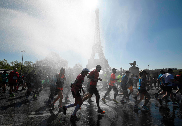 Runners go through a cooling water stream as they compete in the 41 st Paris Marathon in front of the Eiffel tower in Paris on April 9, 2017. (Photo by Eric Feferberg/AFP Photo)