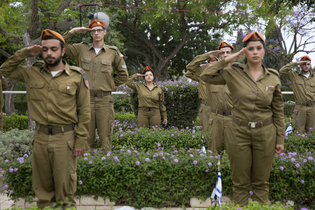 Israeli soldiers salute after placing small flags on the grave of fallen soldiers on the eve of memorial Day in Kiryat Shaul military cemetery in Tel Aviv, Israel, Tuesday, May 10, 2016. (Photo by Ariel Schalit/AP Photo)