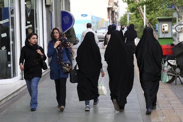 Iranian women make their way along a sidewalk in downtown Tehran, Iran, Tuesday, April 26, 2016. (Photo by Vahid Salemi/AP Photo)
