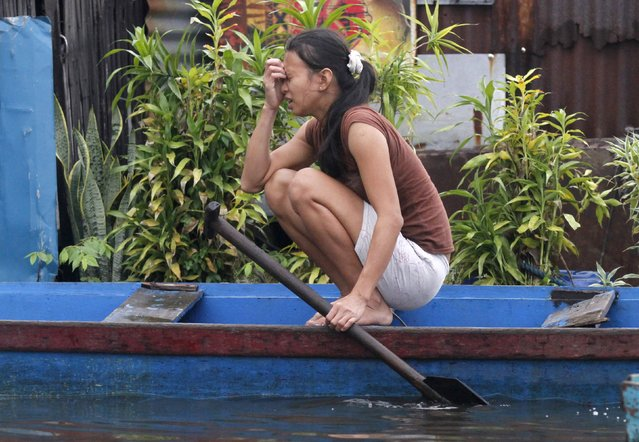 A woman rests on a makeshift boat in Artex Compound, the lowest point in the city, which is prone to flooding during monsoon seasons, in Malabon, Metro Manila in the Philippines July 11, 2015. (Photo by Lorgina Minguito/Reuters)