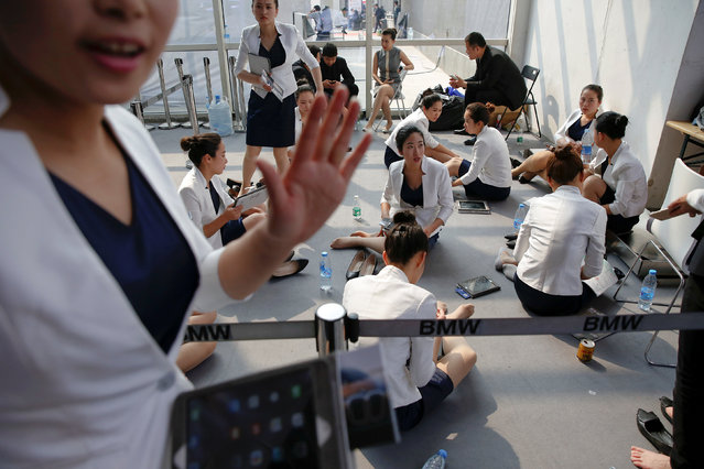 Hostesses rest during the Auto China 2016 auto show in Beijing, China, April 29, 2016. (Photo by Damir Sagolj/Reuters)