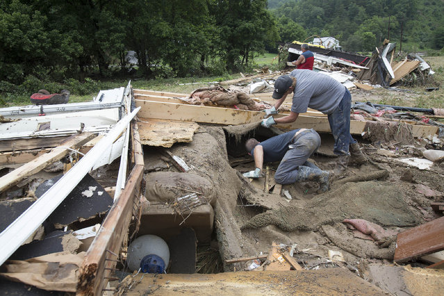 Roland Marcum, left, and Frankie Staton look for Marcum's brother-in-law Scott Johnson under the debris of Marcum's father-in-law's mobile home after deadly flooding in Flat Gap, Ky., Wednesday, July 15, 2015. Family members have been looking for Johnson after he helped saved the lives of four family members but went missing during flash floods in northern Johnson County outside of Paintsville. (Photo by David Stephenson/AP Photo)