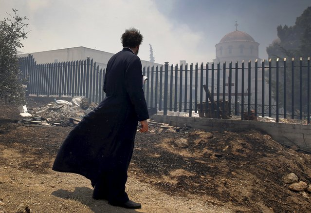 A Greek Orthodox priest stands in a safe location away from a forest fire close to Saint George church (background) in an Athens neighborhood during a forest fire July 17, 2015. (Photo by Yannis Behrakis/Reuters)