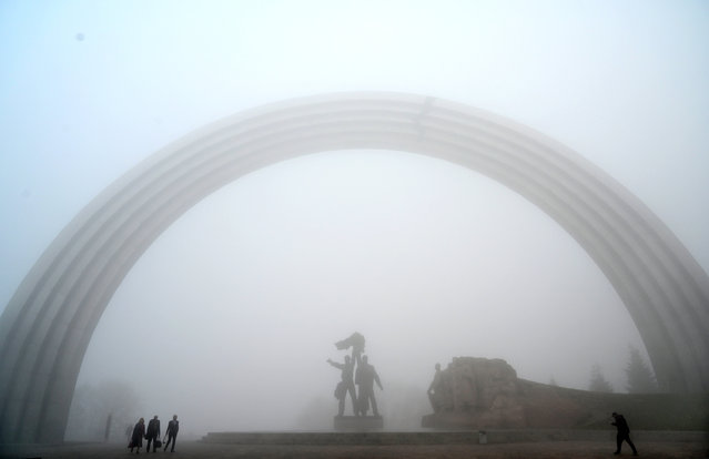 People walk next to a Soviet Era monument during heavy fog in the center of Ukrainian capital of Kiev on October 24, 2019. (Photo by Sergei Supinsky/AFP Photo)