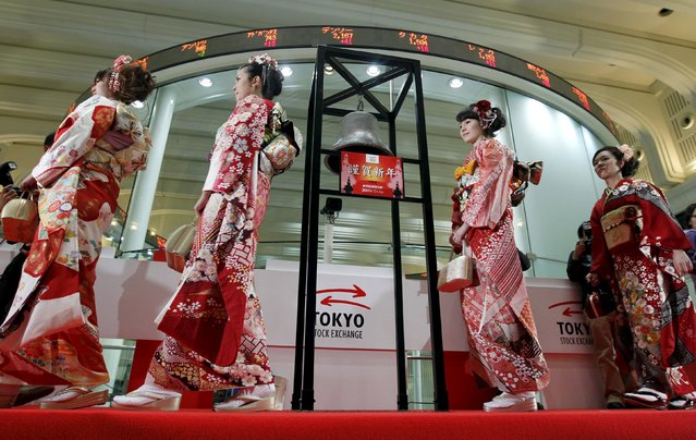 "Women dressed in ceremonial kimonos walk past an electronic board showing stock prices at the Tokyo Stock Exchange's (TSE) New Year opening ceremony in Tokyo in this January 4, 2012 file photo. The diverging performance of Japan's benchmark Nikkei stock average and the broader Topix is a reminder that corporate Japan is not all equally riding the wave of optimism sparked by ""Abenomics"" yet. (Photo by Kim Kyung-Hoon/Reuters)"