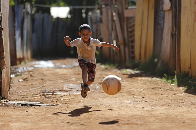 Carlos Lucas kicks a ball along a dirt road in the Santa Luzia favela, in Brasilia, Brazil, on May 30, 2014. The 2014 Brazil World Cup is set to begin in just a few weeks, with Brazil and Croatia competing in the opening match on June 12. (AP Photo/Eraldo Peres)