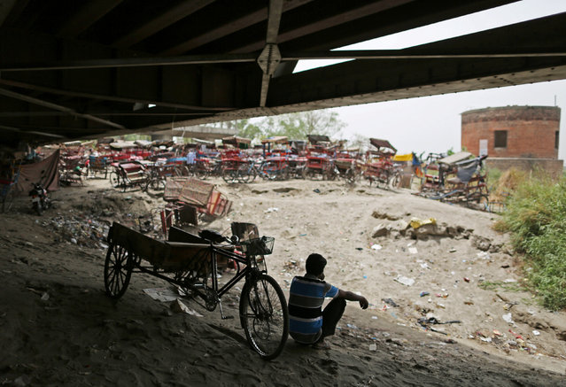 A rickshaw puller sits outside a makeshift cinema located under a bridge in the old quarters of Delhi, India May 25, 2016. (Photo by Cathal McNaughton/Reuters)