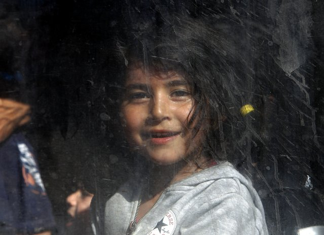 In this photo taken on Thursday, July 23, 2015 a migrant girl looks through a window of a train departing to Serbia from the railway station of Gevgelija, southern Macedonia. (Photo by Boris Grdanoski/AP Photo)