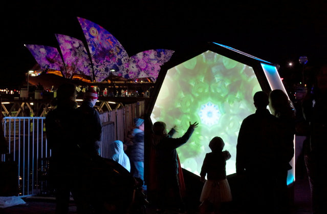 Children interact with a lighted sculpture in front of the Sydney Opera House on the second night of the annual Vivid Sydney light festival in Sydney, Australia, May 28, 2016. (Photo by Jason Reed/Reuters)