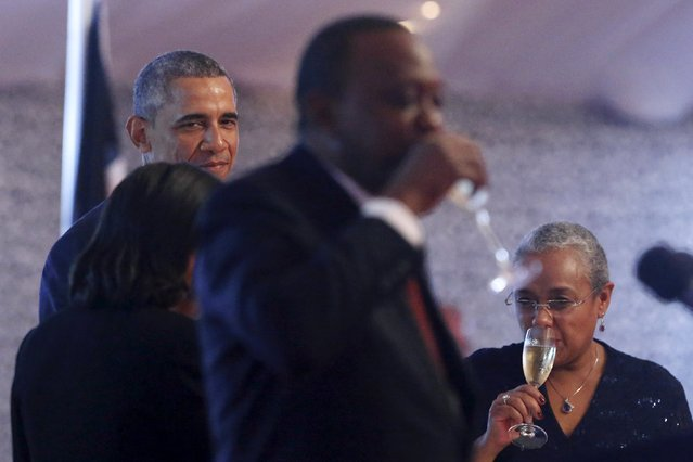 U.S. President Barack Obama (L) looks on as Kenya's President Uhuru Kenyatta (C) drinks a toast to him at the end of a state dinner in Obama's honor at the State House in Nairobi July 25, 2015. Also pictured is Kenyatta's wife Margaret Kenyatta. (Photo by Jonathan Ernst/Reuters)