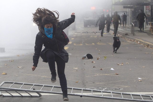 Students clash with riot police during a protest against the Government's education reform in Santiago on June 10, 2014. (Photo by Claudio Reyes/AFP Photo)