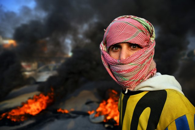 An Iraqi demonstrator is seen at a roadblock with burning tyres in the central holy shrine city of Najaf on November 27, 2019, amid ongoing anti-government demonstrations. Public anger over a lack of jobs triggered as of October 1 an unprecedented grassroots protest movement, Iraq's most widespread and deadly in decades, with persistent rallies demanding deep-rooted regime change across Baghdad and southern Iraq, leaving more than 350 people dead and around 15,000 wounded. (Photo by Haidar Hamdani/AFP Photo)