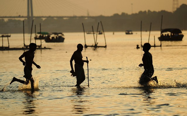 Indian residents wade through waters at Sangam, the confluence of the rivers Ganges, Yamuna and the mythical Saraswati, in Allahabad on June 2, 2014. Allahabad, located in the north Indian state of Uttar Pradesh and where the Ganges, Yamuna and Saraswati rivers meet, is a focal point for Hindu pilgrims where they gather to bathe in the holy waters of the three rivers. (Photo by Sanjay Kanojia/AFP Photo)