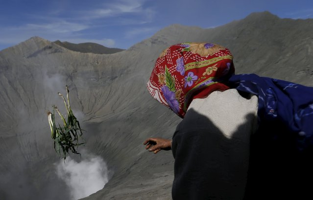 A Hindu worshipper throws vegetables into the crater as offerings during the Kasada Festival at Mount Bromo in Probolinggo, Indonesia's East Java province, August 1, 2015. (Photo by Reuters/Beawiharta)
