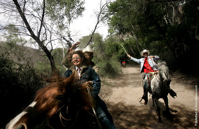 """Arided Martinez, 16, lets go of a nervous smile as Jesus Icedo, 16, directs the horse they are riding into a full gallop. The pair were riding in a 32 kilometer """"cabalgata"""" or horseback ride that was organized by the state of Sonora to celebrate the agrarian roots off the state"""