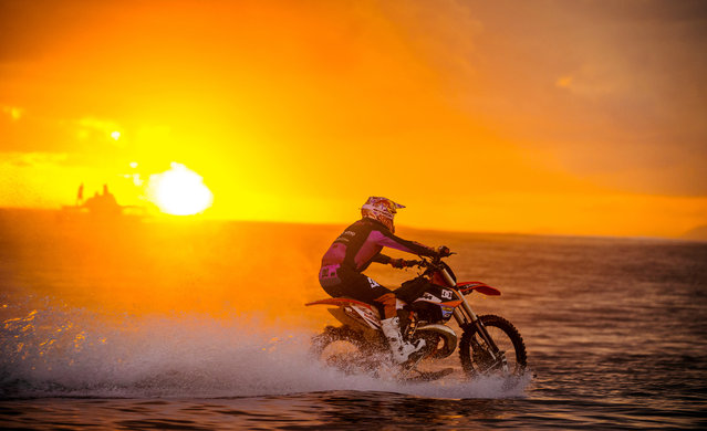 In this April, 2015, photo provided by DC Shoes, daredevil Robbie Maddison in his latest stunt rides his motorcycle across waves in Tahiti, French Polynesia, using ski-like devices on his wheels. (Photo by Mike Blabac/DC Shoes via AP Photo)