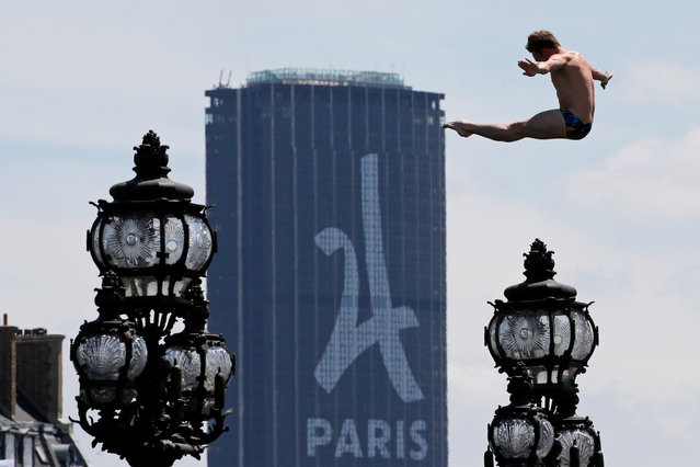 A diver jumps into the River Seine with the Montparnasse tower in the background in Paris, France, June 23, 2017 as Paris transforms into a giant Olympic park to celebrate International Olympic Days with a variety of sporting events for the public across the city during two days as the city bids to host the 2024 Olympic and Paralympic Games. (Photo by Jean-Paul Pelissier/Reuters)