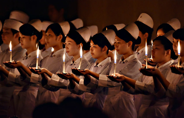 Students of nursing schools hold candles during a candlelight ceremony before starting the awarding ceremony for the Florence Nightingale medal in Tokyo on August 5, 2015. (Photo by Yoshikazu Tsuno/AFP Photo)