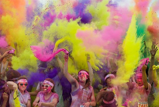 """Participants are doused in colors at the finish of the Color Run, a 5-kilometer (3-mile) run at the Great Park in Irvine, Calif., April 22. Racers begin the run in white shirts and as they pass each kilometer they are doused by volunteers with a different color of """"magical"""" dust"""