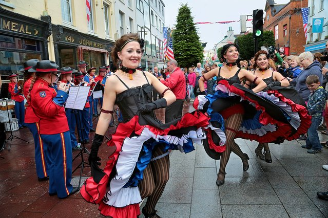 """Members of the WIld West Troupe, from Cahirciveen, Ireland, performing the """"Can Can"""" with the Crumlin Brass Band as part of the Killarney 4th July Celebrations on Friday in the town centre, on Jule 4, 2014. (Photo by Valerie O'Sullivan/PA Wire)"""