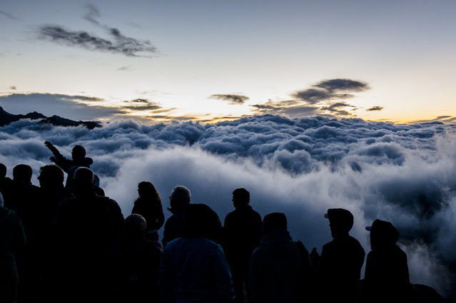 Tourists watch the sunrise above a sea of fog on Eggishorn moutain (2927 meters over sea level), in Fiesch, Switzerland, early Tuesday, July 28, 2015. (Photo by Dominic Steinmann/Keystone via AP Photo)