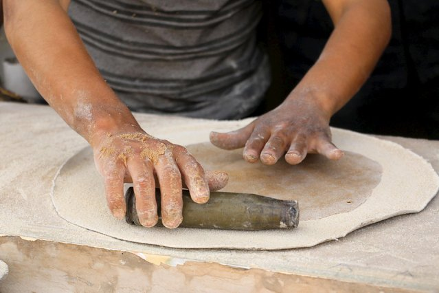 "A boy uses remnants of ordnance as he prepares dough inside Abu Khaled's shop in the Douma neighborhood of Damascus April 28, 2015. Abu Khaled opened a shop for making ""barley bread"" using remnants of weapons including rockets, tank shells and other ordnance fired by forces loyal to Syria's President Bashar al-Assad. (Photo by Amer Almohibany/Reuters)"