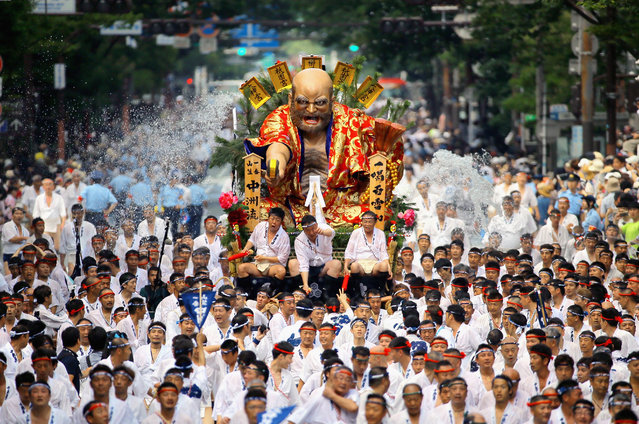 """Men runs with a Hikiyama float during the """"Shudan Kaomise"""" event as a part of the Hakata Gion Yamakasa on July 13, 2017 in Fukuoka, Japan. The Yamakasa festival concludes with the """"Oiyama"""" race, highlight of the festival on July 15. (Photo by The Asahi Shimbun via Getty Images)"""