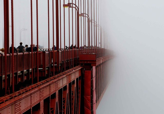 The span of the Golden Gate Bridge disappears into the fog on June 27, 2014 in San Francisco, California. The Golden Gate Bridge district's board of directors voted unanimously to approve a $76 million funding package to build a net suicide barrier on the iconic span. Over 1,500 people committed suicide by jumping from the iconic bridge since it opened in 1937. 46 people jumped to their death in 2013. (Photo by Justin Sullivan/AFP Photo)