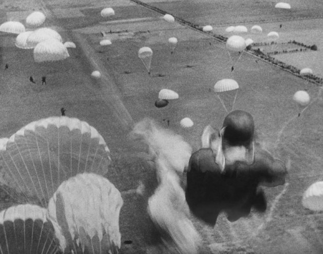 An American paratrooper (right foreground) leaps from a plane during maneuvers in North Africa, July 17, 1943 preceding the allied invasion of Sicily. Other paratroopers and chutes are seen in background. (Photo by AP Photo)