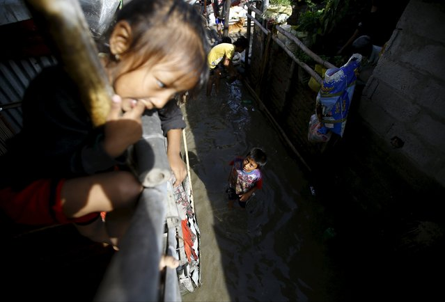 A boy speaks with a girl as he stands in floodwaters flowing from the swollen Bagmati River due to heavy rainfall, in a slum in Kathmandu, Nepal August 17, 2015. (Photo by Navesh Chitrakar/Reuters)