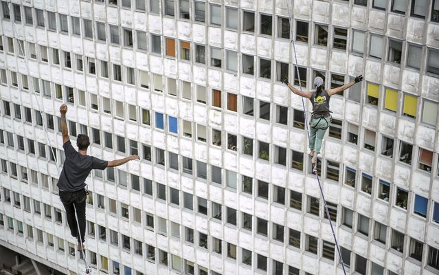 Slackliners walk on a slackline across skyscrapers during the 6th Urban Highline Festival in Lublin, Poland, July 26, 2014. (Photo by Wojciech Pacewicz/EPA)
