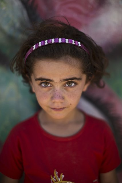 In this Tuesday, July 29, 2014, photo, Syrian refugee Samah, 5, poses for a picture at Zaatari refugee camp, near the Syrian border, in Mafraq, Jordan. More than 2.8 million Syrian children inside and outside the country – nearly half the school-aged population – cannot get an education because of the devastation from the civil war, according to the U.N. children's agency, UNICEF. (Photo by Muhammed Muheisen/AP Photo)