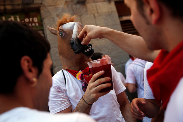 A reveller attempts to drink without removing his horse mask during the start of the San Fermin festival in Pamplona, northern Spain, July 6, 2016. (Photo by Susana Vera/Reuters)