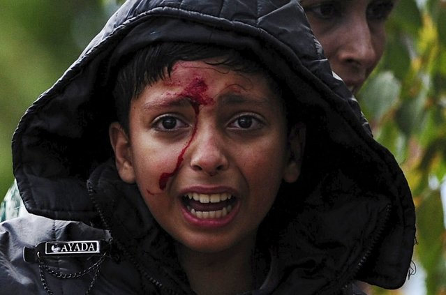 A girl cries after crossing Greece's border into Macedonia near Gevgelija, Macedonia, August 22, 2015. Thousands of migrants stormed across Macedonia's border on Saturday, overwhelming security forces who threw stun grenades and lashed out with batons in an increasingly futile bid to stem their flow through the Balkans to western Europe. (Photo by Ognen Teofilovski/Reuters)