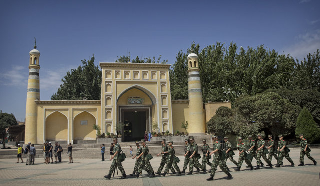 Chinese soldiers march in front of the Id Kah Mosque, China's largest, on July 31, 2014 in Kashgar, China. China has increased security in many parts of the restive Xinjiang province following some of the worst violence in months in the Uyghur dominated area. (Photo by Kevin Frayer/Getty Images)