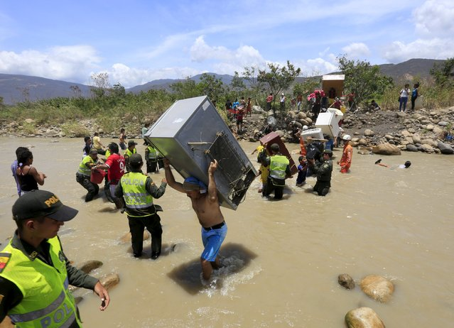A man carries a refrigerator while crossing the Tachira river border with Venezuela into Colombia, near Villa del Rosario village August 25, 2015. The ongoing crisis on the border between Colombia and Venezuela should not be used for political point-scoring by leaders in either country ahead of elections in coming months, the Colombian government said on Tuesday. (Photo by Jose Miguel Gomez/Reuters)