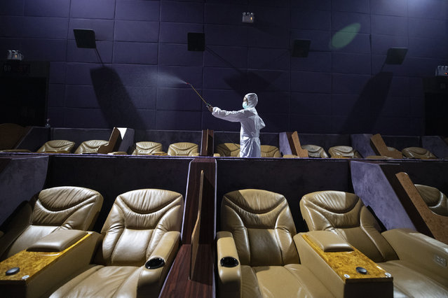 A worker sprays disinfectant as a precaution against the new coronavirus at Quartier Cineart movie theater in Bangkok, Thailand, Thursday, March 19, 2020. Thailand's government has enacted stronger measures to combat the spread of the coronavirus, including postponing the country's biggest holiday, shutting down schools, movie theaters and closing bars. (Photo by Sakchai Lalit/AP Photo)