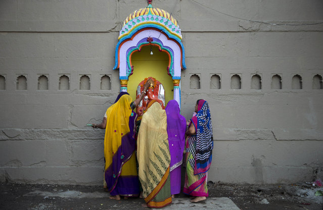 Indian women pray to an idol of elephant-headed Hindu god Ganesha at the Kumbh Mela, or Pitcher Festival, in Nasik, India, Thursday, August 27, 2015. Millions are expected to attend this year's two-month festival, which began in mid-July and runs until the end of September. The festival is held four times every 12 years. (Photo by Tsering Topgyal/AP Photo)