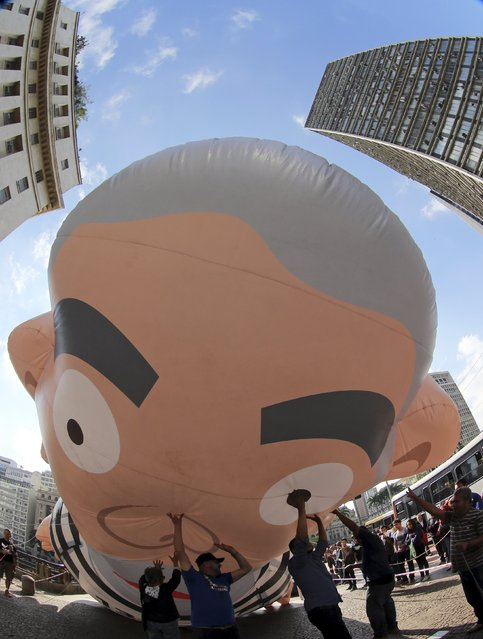 People raise up a giant inflatable doll that depicts former Brazilian President Luiz Inacio Lula da Silva in prison attire during a protest against Brazil's President Dilma Rousseff and the Workers' Party in downtown Sao Paulo, Brazil, August 28, 2015. Brazil's economy shrank 1.9 percent in the second quarter, sinking into a recession that has hammered Rousseff's popularity as she struggles to save the country's investment-grade credit rating amid a vast corruption scandal. (Photo by Paulo Whitaker/Reuters)