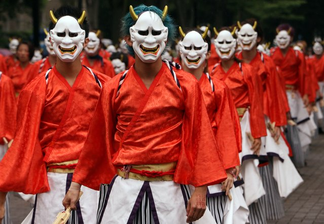 "Dancers wearing masks and kimonos perform in the streets at the ""Super Yosakoi 2015"" dance festival in Tokyo on August 30, 2015. One hundred dance teams with some 5,500 people participated in the two-day summer festival event. (Photo by Yoshikazu Tsuno/AFP Photo)"