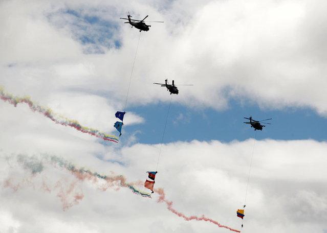 Soldiers hang on a rope with flags as a military helicopter performs a flypast during a military parade to celebrate the 206th anniversary of Colombia's independence in Bogota, Colombia, July 20, 2016. (Photo by John Vizcaino/Reuters)