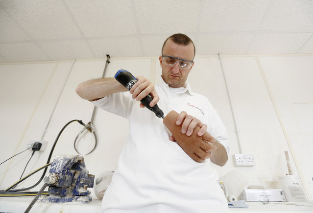 Custom silicone technician Corin Watts works on a prosthetic partial hand at the London Prosthetic Centre in Kingston-Upon-Thames, southwest London, August 12, 2014. (Photo by Luke MacGregor/Reuters)