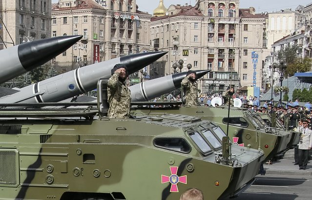 Soldiers salute as they parade on Tochka-U tactical rocket complexes during Ukraine's Independence Day military parade in the centre of Kiev August 24, 2014. Armored vehicles and soldiers, some of them hardened in battle, paraded on Kiev's main square on Sunday to mark Independence Day in a defiant show of the military force Ukraine's government hopes will defeat pro-Russian separatists in the east. (Photo by Gleb Garanich/Reuters)