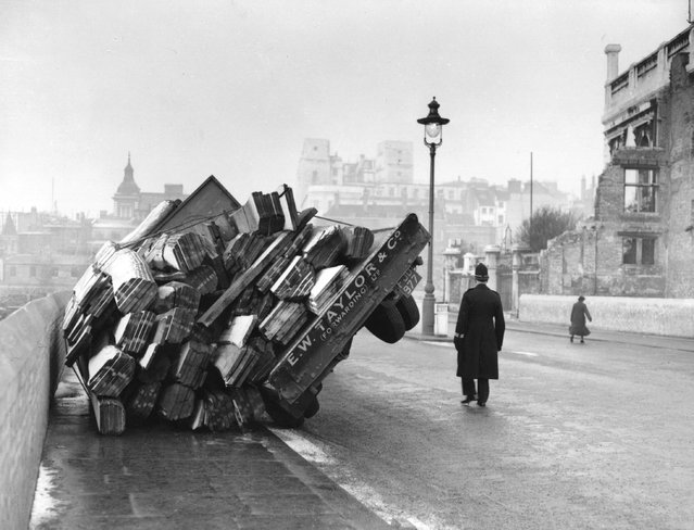 A lorry loaded with timber, overturned in icy conditions in Queen Victoria Street, London, 1955. (Photo by L. Blandford)