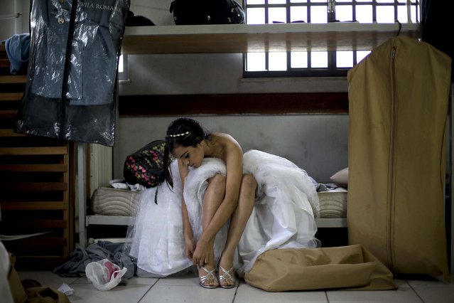 A teenage girl from the Santa Marta favela slum puts on a pair of high heels for a group debutante ball organized by the Pacifying Police Unit from her neighborhood in Rio de Janeiro, Brazil, Friday, August 29, 2014. The ball, which relied on volunteers who coiffed and made up the girls and a formal wear shop that loaned the dresses, helped build goodwill between pacified favelas' residents and the officers who patrol them. (Photo by Silvia Izquierdo/AP Photo via The Palm Beach Post)