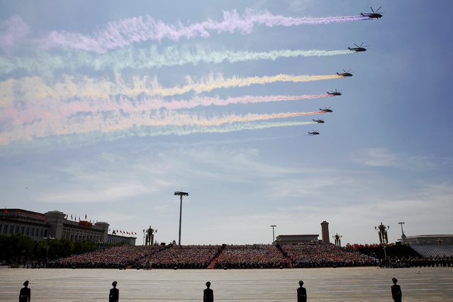 People watch and paramilitary policemen stand guard as military helicopters fly over the Tiananmen Square during the military parade marking the 70th anniversary of the end of World War Two, in Beijing, China, September 3, 2015. (Photo by Damir Sagolj/Reuters)