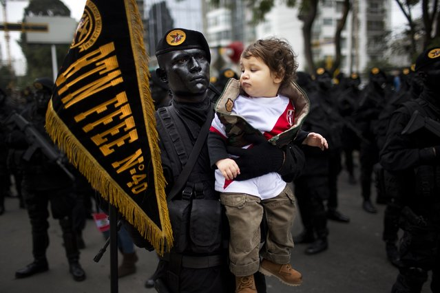 Intor Montoro Carba, 20, a military special forces officer, holds Jeremy Bock, at the request of Jeremy's parents who wanted to make a photo of their son with the striking soldier, before the start of a military parade marking the country's Independence Day in Lima, Peru, Friday, July 29, 2016. Peru declared it's independence from Spain in 1821. (Photo by Rodrigo Abd/AP Photo)