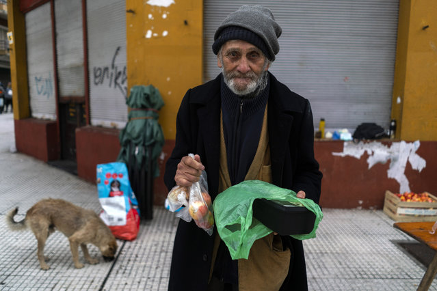 A man poses for a photo holding food he received from a group of neighbors who have formed to help people in need facing hardship amid the new coronavirus pandemic, in the financial district of Montevideo, Uruguay, Saturday, April 25, 2020. (Photo by Matilde Campodonico/AP Photo)