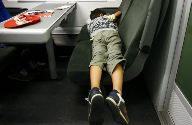 A migrant boy sleeps aboard a train to Vienna departed from the railway station in the town of Hegyeshalom, Hungary, September 5, 2015. (Photo by Leonhard Foeger/Reuters)